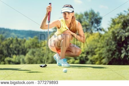 Woman on golf course taking measure on the green being careful not to lose the shot