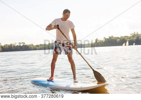 Portrait Of A Surfer With A Sup Board On The Beach. Young Man On Paddleboard At Dawn. The Concept Of