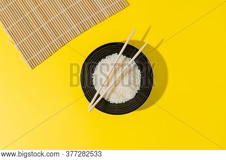 Plate With White Rice. Chopsticks, Bamboo Mat. Black Plate With White Rice On A Yellow Background. C