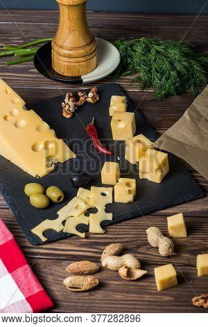 Maasdamer Cheese. Diced Cheese On A Cheese Platter, Nuts, Herbs, Olives On An Old Black Wooden Table