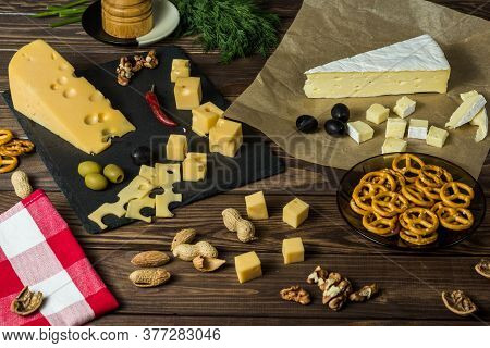 Brie Cheese Maasdamer Cheese. Diced Cheese On A Cheese Platter, Nuts, Herbs, Olives, Snacks On An Ol