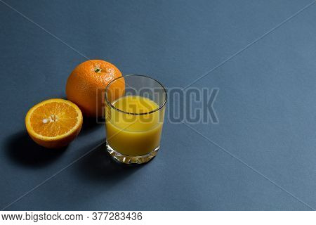 Orange Juice And Sliced ​​orange. A Glass Of Orange Juice, A Whole Orange And A Sliced ​​orange On A