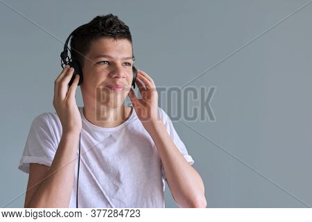 Portrait Of Teenage Boy 16 Years Old In Headphones Listening To Music, Audiobooks, Lessons. Gray Ins