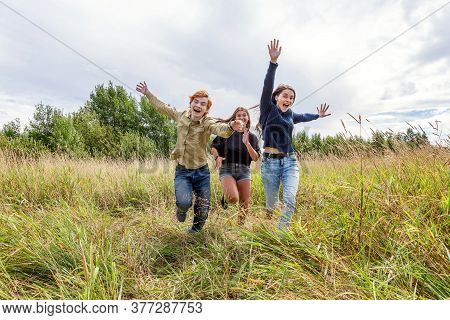 Summer Holidays Vacation Happy People Concept. Group Of Three Friends Boy And Two Girls Running And
