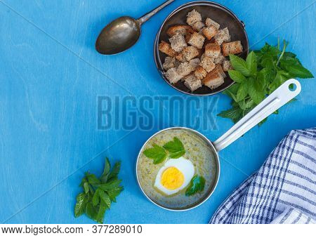 Vegetarian Cream Of Wild Greens Soup In A Ladle And A Copper Bowl With Crackers On A Blue Background