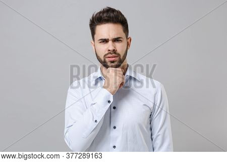 Puzzled Young Unshaven Business Man In Light Shirt Posing Isolated On Grey Wall Background Studio Po