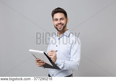 Cheerful Young Unshaven Business Man In Light Shirt Posing Isolated On Grey Background. Achievement