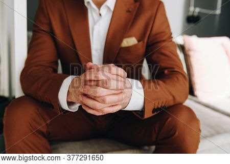 Closeup Of Hands Young Caucasian Man In Elegant Brown Suit With His Fingers Intertwined, Worrying An
