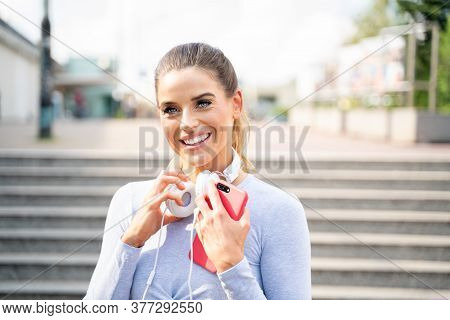 Fit Smiling Girl Listening Music On The City Street.