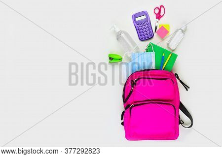 Backpack With School Supplies And Covid 19 Prevention Items. Top View, Spilling Onto A White Backgro