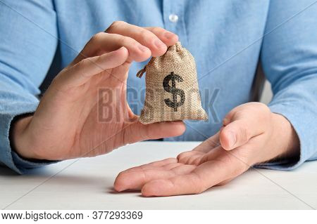 A Hand In A Shirt Holds A Small Bag With Money And A Usa Dollar Sign