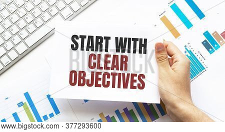 Businessman Holding A Card With Text Start With Clear Objectives. Keyboard, Diagram And White Backgr