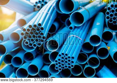 Selective To Blue Plastic Pipe Background. Pvc Pipes Stacked In Warehouse Of Construction Site.