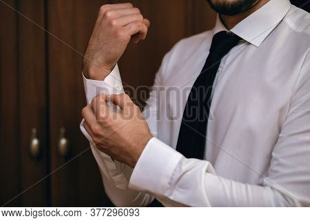 A Man Fastens The Sleeves Of His Shirt, Close-up, White Shirt, On A Brown Background, Stylish Male B