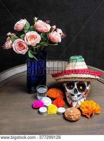 Hand Painted Skull With A Hat, Roses In A Vase, Colorful Paper Flowers, Mezcal, Candles, And Brad On