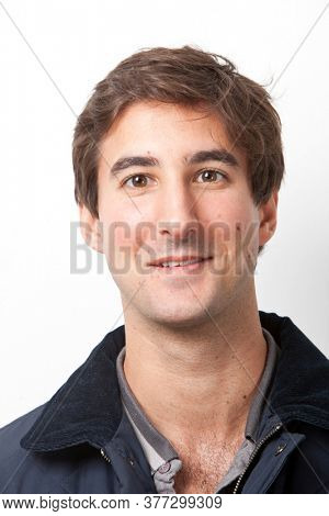 Portrait of handsome Middle Eastern young man smiling against white background