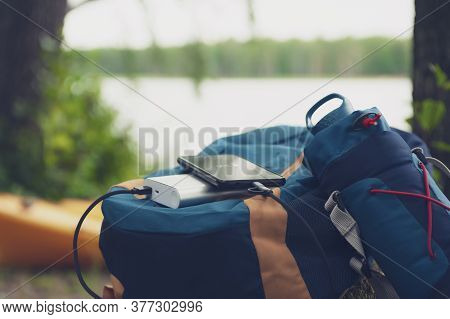 Portable Travel Charger. Power Bank Charges Smartphone Against A Backdrop Of Journey Bags, A Lake An