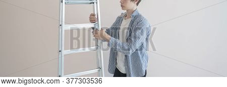 A Worker Man Holding The Aluminium Ladder Against The Wall In The New House