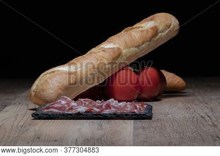 Typical Spanish Ham On A Dark Plate With A Bread Loaf And Tomatoes In The Back On A Wooden Table.