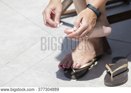Female Hands Holding A Cotton Pad Stained With Nail Polish Next To Her Feet. Hygiene And Makeup Conc