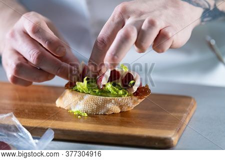 Male Hands Preparing An Open Sandwich With Lettuce, Caramelized Onion And Ham. Healthy Food Concept.