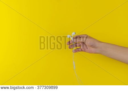 A Persons Hand Holding Portable Wired Earphones Or Headphones Isolated Against The Colorful Backgrou