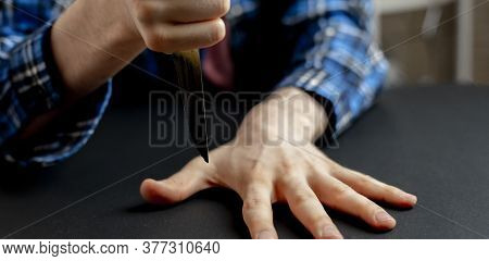 Hand With Knife Hitting Between The Fingers On The Table, Playing The Game With A Sharp Blade Wide W