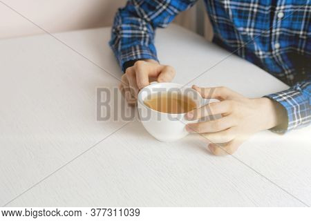 A Person Sitting At The Table And Drink Cup Of Tea At Home In The Evening