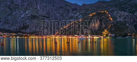 Sunset Of Kotor Bay Or Boka Kotorska With An Illuminated Ancient Fortress City Wall In The Mountains