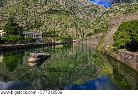 Emerald Green Waters Of Kotor Bay Or Boka Kotorska, Mountains And The Ancient Stone City Wall Of Kot