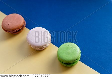 Colorful Cake Macaron Or Macaroon, White Meringues On Blue, Yellow Background. French Almond Cookies