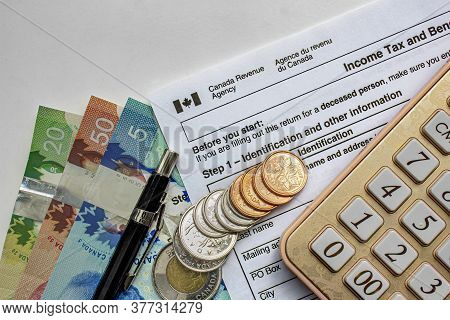 Calgary, Alberta, Canada. July 20, 2020. Canadian Tax Forms With Coins, Calculator, A Pen And Bills