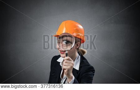 Technical Inspector Looking Through Magnifying Glass. Woman Civil Engineer In Orange Safety Helmet C
