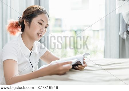 Asian Woman Reads An Analog Book On The Sofa In Her House.