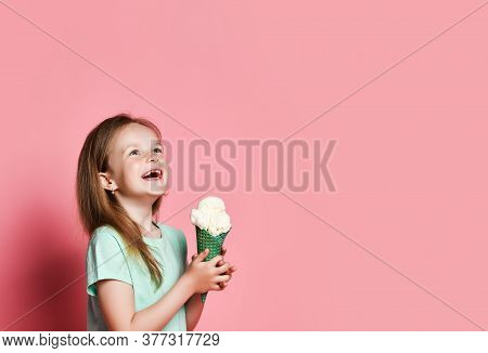 Pretty 6-7 Y.o. Kid Girl In T-shirt Holds Big Vanilla Ice Cream In Waffles Cone With Both Hands Laug