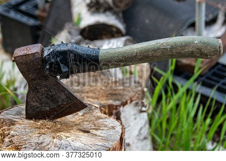 An Old Rusty Ax With A Wooden Handle Is Rewound With A Black Ribbon, Stuck In A Birch Stump Against