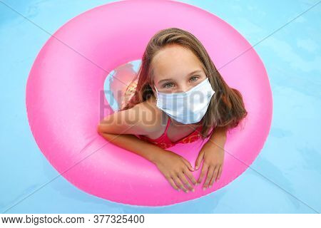 Girl With Medical Mask On Her Face In Pool.