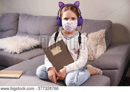 Little Girl Protective Mask. Got Ready To Go To School. Schoolgirl With A Backpack, Books For The Sc