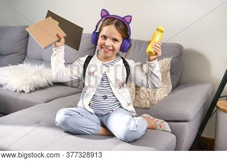 Little Girl Musical Headphones Got Ready To Go To School. Schoolgirl With A Backpack, Books And A Sn