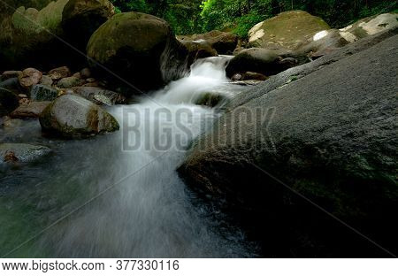Waterfall Is Flowing In Jungle. Rock Or Stone At Waterfall. Waterfall In Tropical Forest. Nature Bac