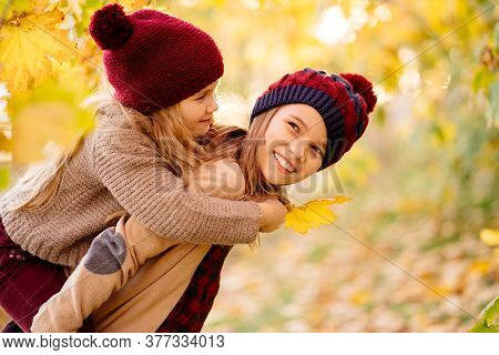 Two Girls In Hats Are Playing And Having Fun In Autumn Park Under Yellow Maples. The Older Sister Ro