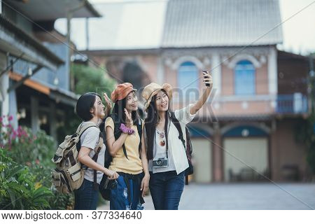 Asian Woman Group Backpacker Take A Selfie On Street Together, Friendship Traveller Backpack Travel