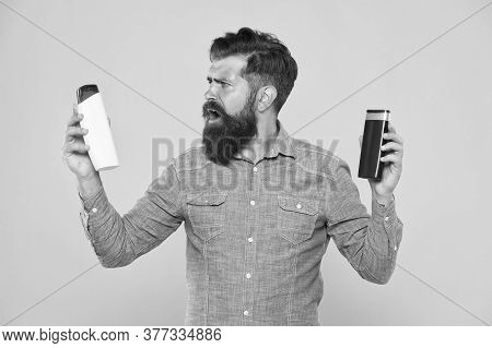 Shampooing Hair In Salon. Bearded Man Choose Shampoo To Use. Daily Shampooing Habits. After Shampooi
