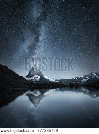 Matterhorn And Reflection On The Water Surface At The Night Time. Milky Way Above Matterhorn, Switze