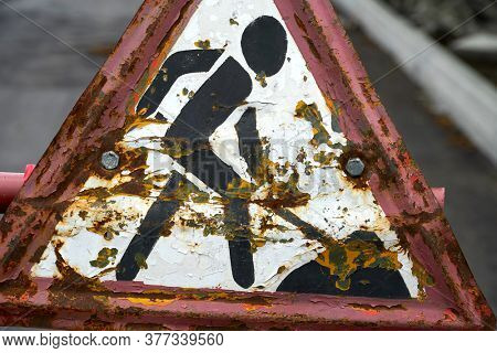 road work warning sign, old or obsolete object closeup