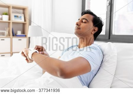 technology, bedtime and rest concept - happy smiling indian man with smart watch doing breath exercise lying in bed at home