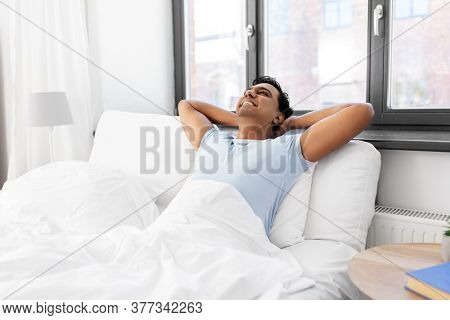 people, bedtime and rest concept - happy smiling relaxed indian man stretching in bed at home