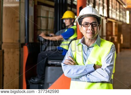 Portrait of Asian warehouse manager stand and arm crossed in distribution warehouse with warehouse worker operate forklift in background. Reopening business warehouse technology and logistic concept.