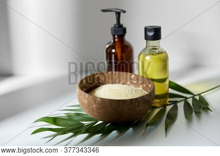natural cosmetics, sustainability and eco living concept - sea salt in bowl, liquid soap or shower gel, massage oil and palm leaf on white background