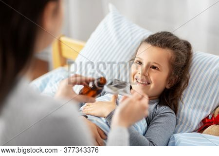 family, health and medicine concept - mother pouring cough syrup for little sick daughter lying in bed at home
